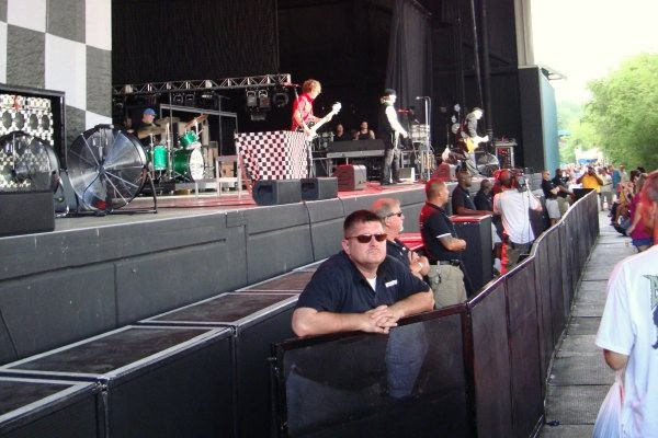 Front stage security and photographers at a Cheap Trick concert.